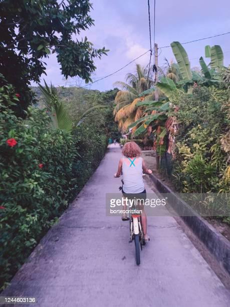 rear view of people riding bicycle on road - bortes fotografías e imágenes de stock