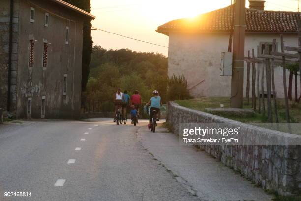 Rear View Of People Riding Bicycles On Road