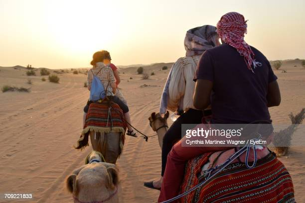 Rear View Of People Riding Camels At Desert During Sunset