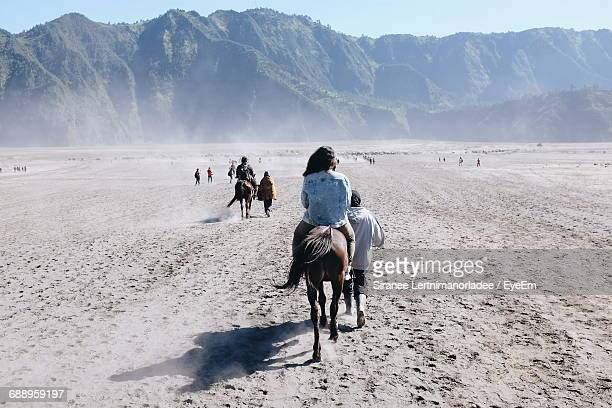rear view of people riding horses at bromo-tengger-semeru national park - mt bromo stock photos and pictures