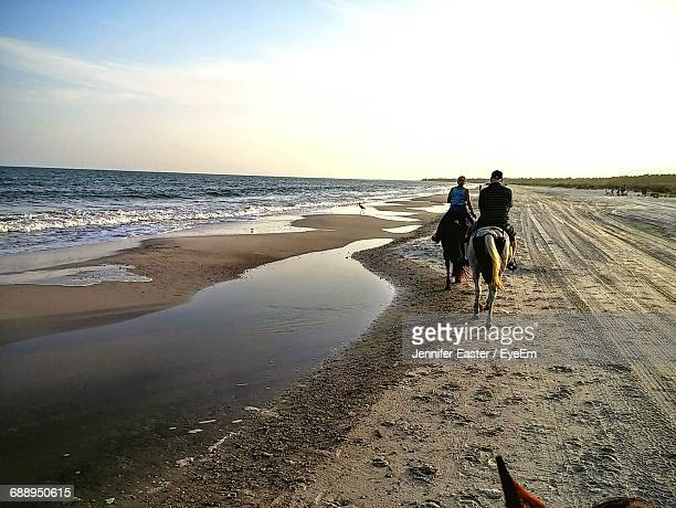 rear view of people riding horses at shore against sky - horse easter stock pictures, royalty-free photos & images