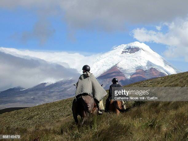 Rear View Of People Riding Horses On Grassy Field Against Cotopaxi