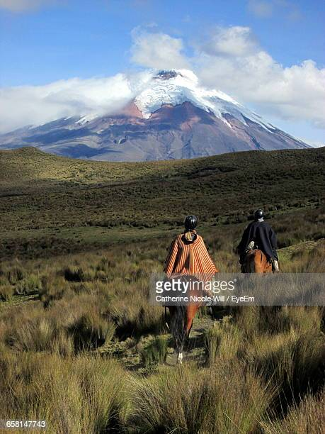 rear view of people riding horses on grassy landscape against cotopaxi - ecuador fotografías e imágenes de stock