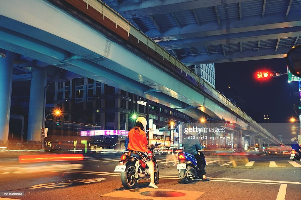 Rear View Of People Riding Motor Vehicles On Road At Night : Stock Photo