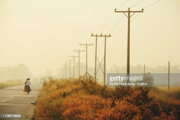 rear view of people riding motorcycle on road against sky during sunset - ko ko htike aung stock pictures, royalty-free photos & images