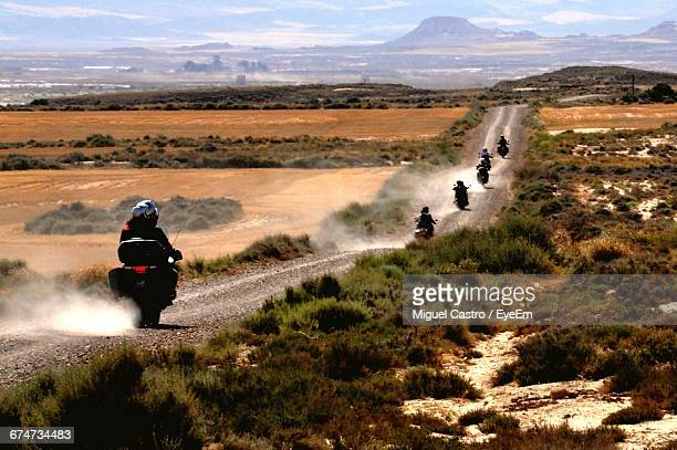 Rear View Of People Riding Motorcycles At Bardenas Reales