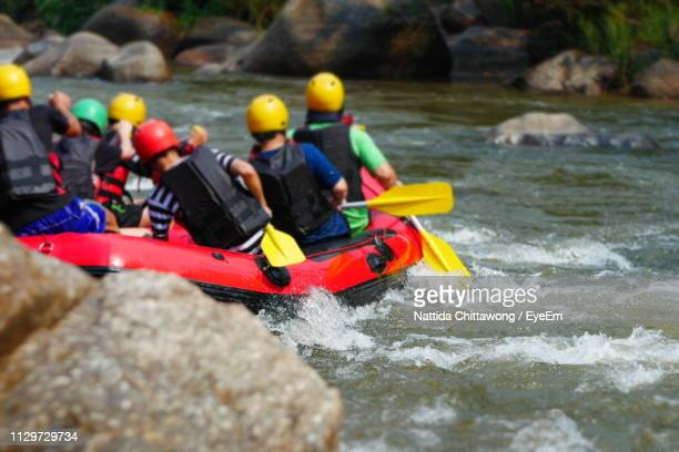 Rear View Of People River Rafting