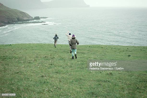 Rear View Of People Running On Grassy Field Against Sea At Neist Point Lighthouse