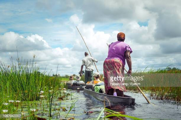 rear view of people sailing in lake against sky - okavango delta stock pictures, royalty-free photos & images