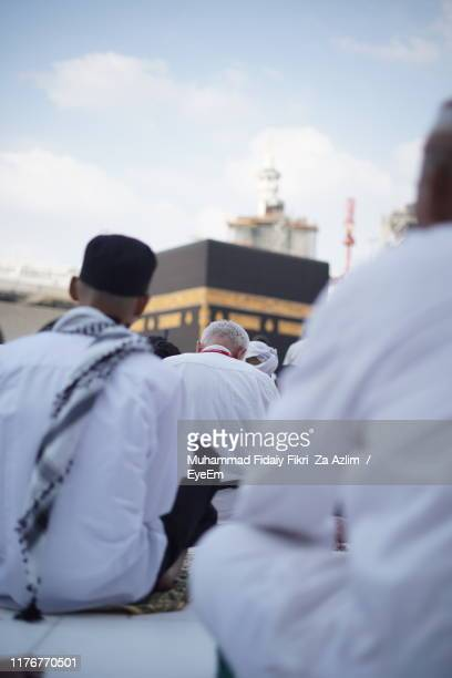 rear view of people sitting against building and sky - mecca stock pictures, royalty-free photos & images