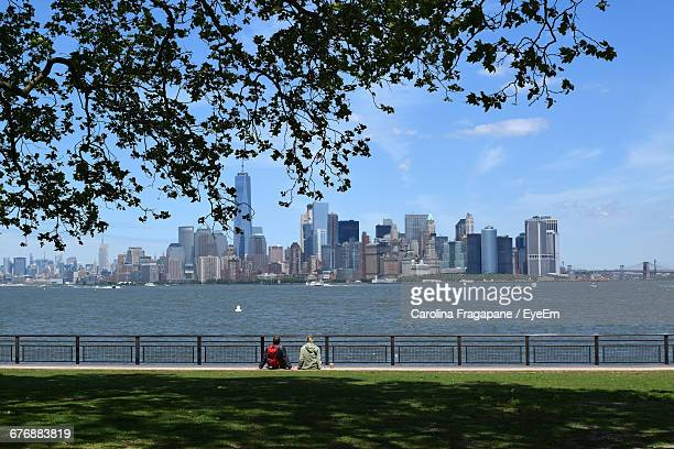 rear view of people sitting at park by hudson river and city skyline against sky - carolina fragapane stock pictures, royalty-free photos & images