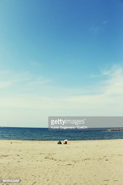 Rear View Of People Sitting At Sandy Beach Against Sky