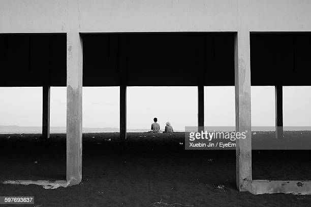 Rear View Of People Sitting By Abandoned Built Structure At Beach