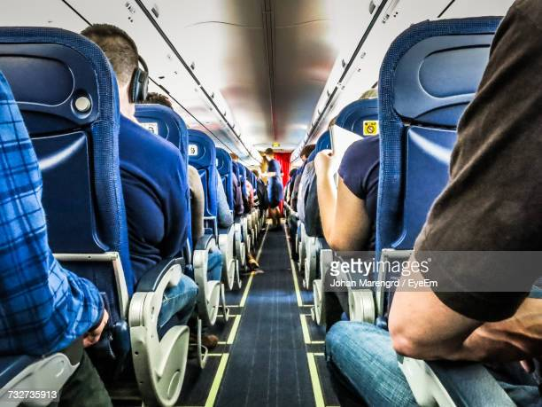 rear view of people sitting in airplane - vehicle interior stock pictures, royalty-free photos & images