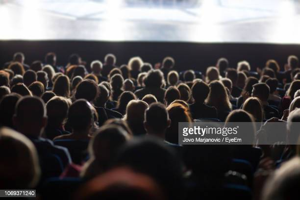 rear view of people sitting in auditorium during seminar - crowd of people stock pictures, royalty-free photos & images