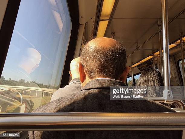 rear view of people sitting in train during sunny day - baum stock pictures, royalty-free photos & images