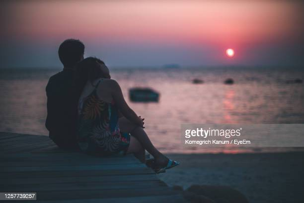 rear view of people sitting on beach during sunset - anniversary stock pictures, royalty-free photos & images