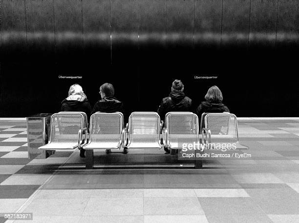 Rear View Of People Sitting On Bench At Railroad Station