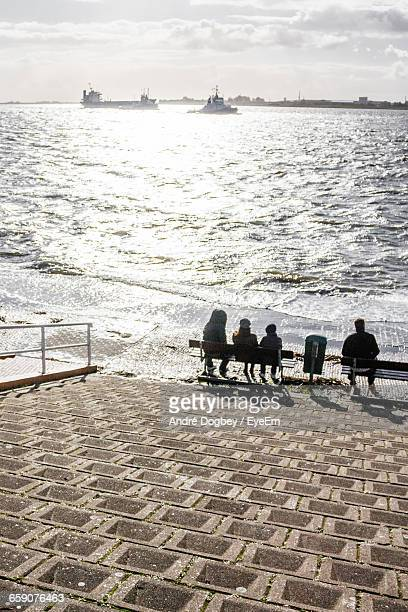 Rear View Of People Sitting On Bench At Riverbank