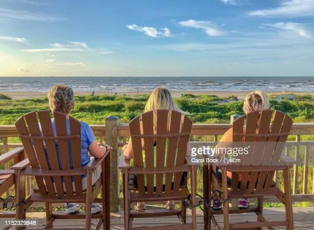 rear view of people sitting on chairs at beach against sky during sunset - galveston stock pictures, royalty-free photos & images