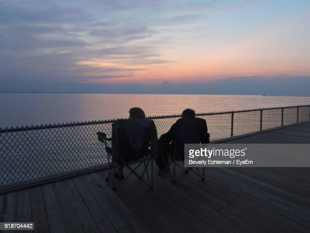 Rear View Of People Sitting On Chairs At Pier Over Sea During Sunset