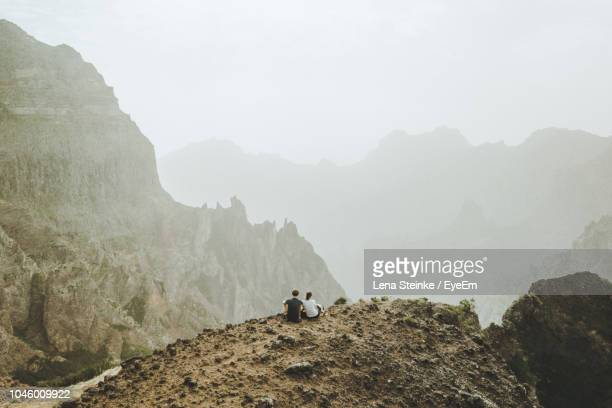 rear view of people sitting on cliff by mountains against sky - lareira stock pictures, royalty-free photos & images