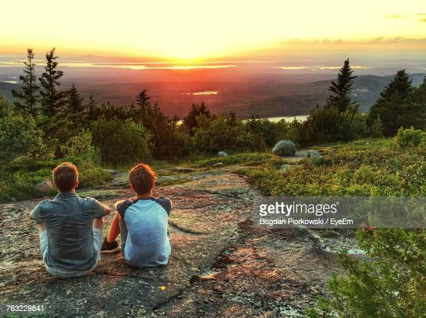 rear view of people sitting on landscape against sky during sunset - bar harbor stock photos and pictures