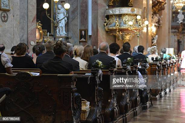 rear view of people sitting on pews in church - kirche stock-fotos und bilder