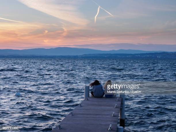 rear view of people sitting on pier over sea against sky during sunset - marek stefunko stock photos and pictures