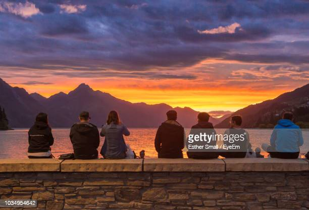 rear view of people sitting on retaining wall against sky during sunset - queenstown stock pictures, royalty-free photos & images
