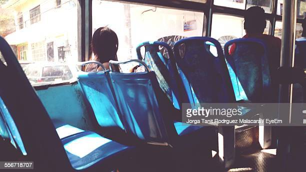Rear View Of People Sitting On Seats In Bus