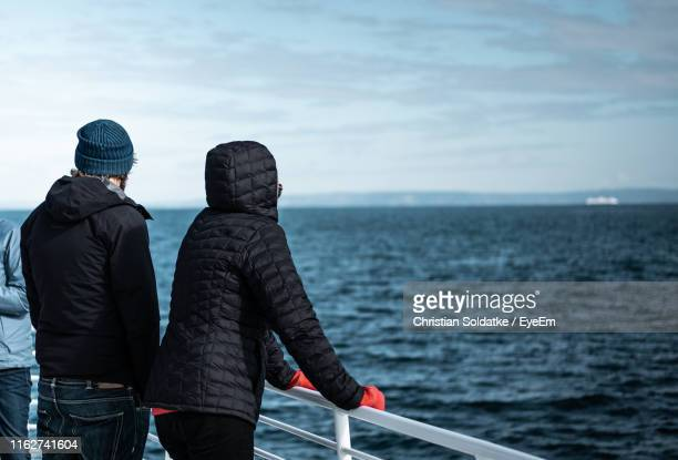 Rear View Of People Standing By Railing Of Nautical Vessel On Sea Against Sky