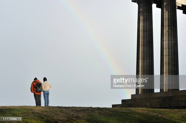 rear view of people standing on land against sky - richard flint stock pictures, royalty-free photos & images