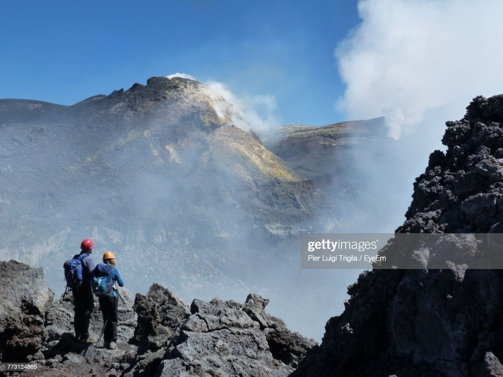 Rear View Of People Standing On Mountain Against Sky : Photo