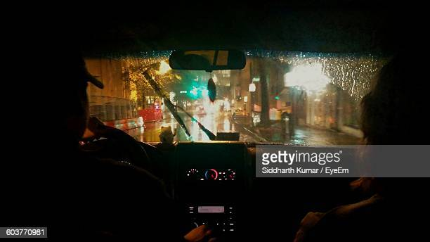 Rear View Of People Traveling In Car At Night During Monsoon