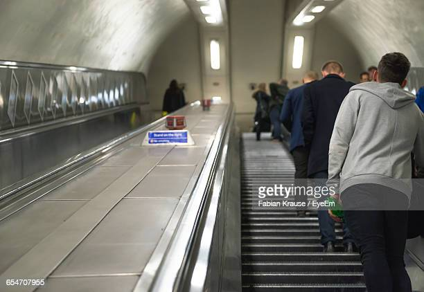 Rear View Of People Traveling On Escalator