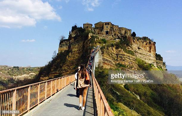 rear view of people walking at civita di bagnoregio - civita di bagnoregio foto e immagini stock