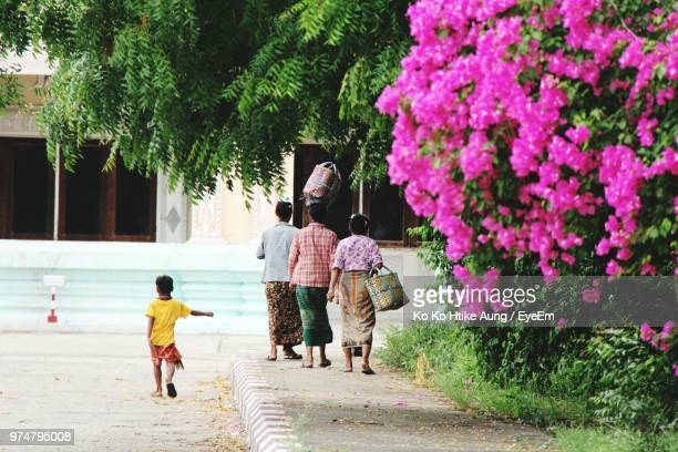 rear view of people walking footpath in city - ko ko htike aung stock pictures, royalty-free photos & images