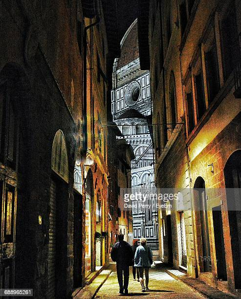 rear view of people walking in illuminated alley against florence cathedral - florence italy stock pictures, royalty-free photos & images