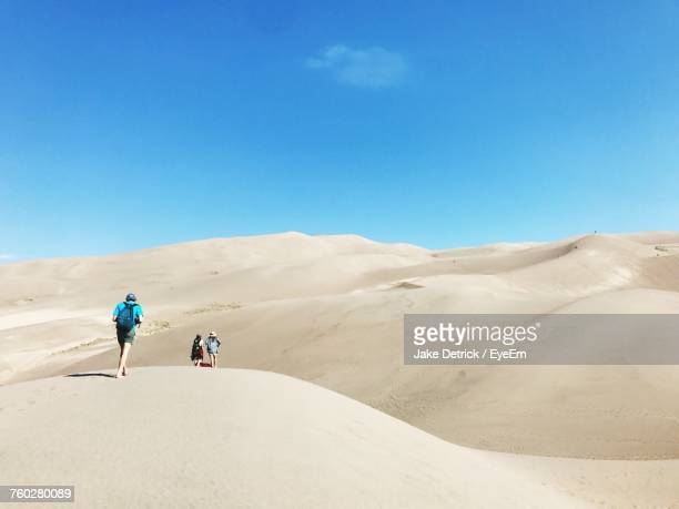 rear view of people walking in the desert - great sand dunes national park stock pictures, royalty-free photos & images