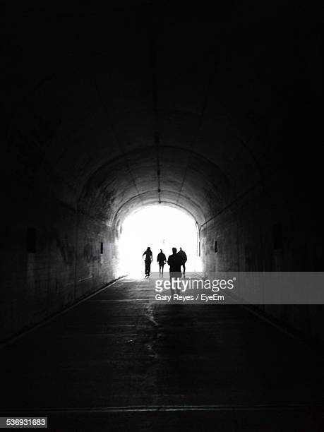 rear view of people walking in tunnel - light at the end of the tunnel stock pictures, royalty-free photos & images