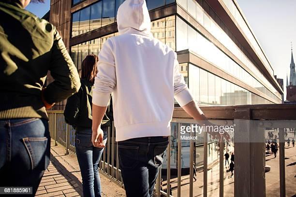 rear view of people walking on bridge against buildings in city - capuchon stockfoto's en -beelden