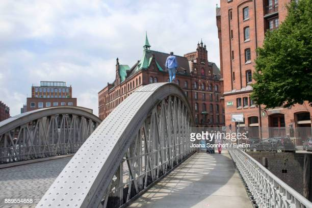 rear view of people walking on bridge against buildings - number of people stock pictures, royalty-free photos & images
