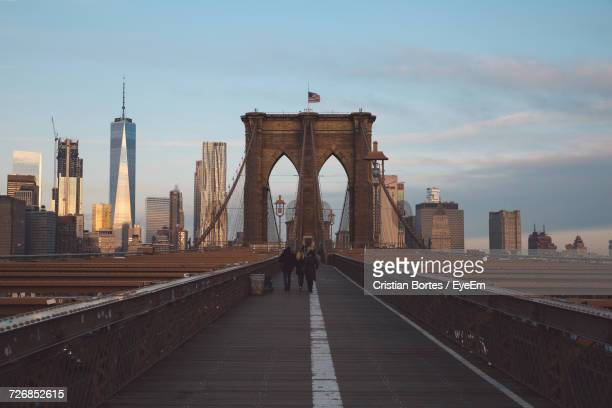 rear view of people walking on brooklyn bridge in city - bortes photos et images de collection