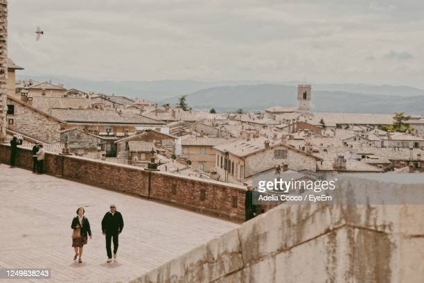 rear view of people walking on buildings in city - gubbio stock pictures, royalty-free photos & images