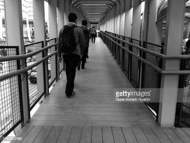 rear view of people walking on footbridge in city - oppie muharti stock pictures, royalty-free photos & images