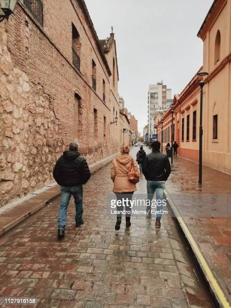 rear view of people walking on footpath amidst buildings - cordoba argentina fotografías e imágenes de stock