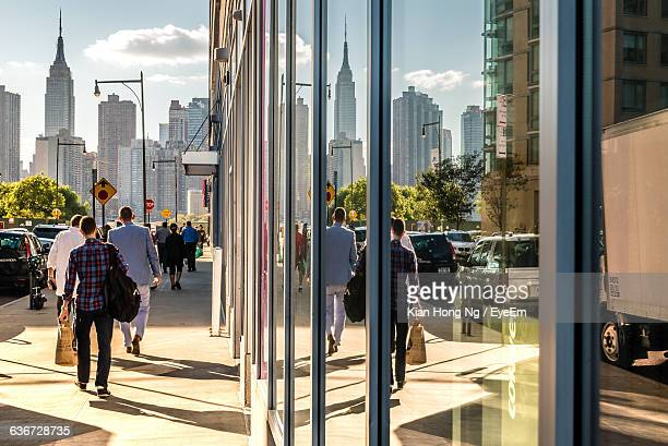Rear View Of People Walking On Footpath By Building