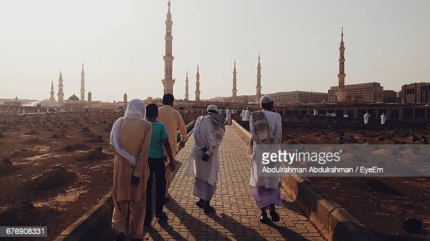 rear view of people walking on footpath by cemeteries against clear sky - riyadh foto e immagini stock