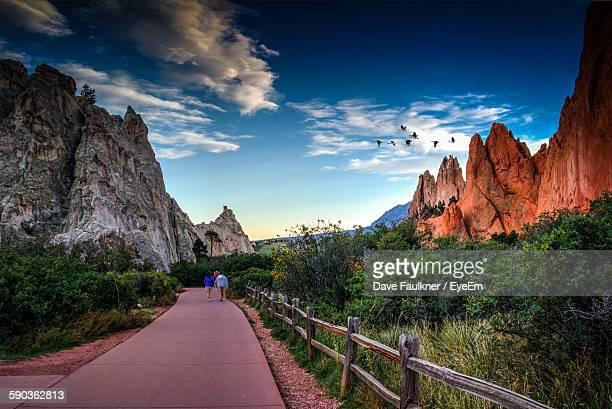 Rear View Of People Walking On Footpath By Rock Formation And Plants Against Sky At Colorado Springs